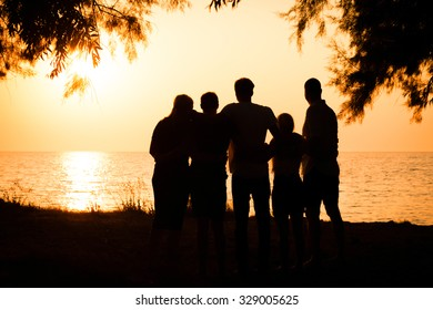 Silhouette of a big family holding each other and watching a beautiful sunset at the seaside in Greece. Concept of traveling together and enjoying the outdoors and the nature