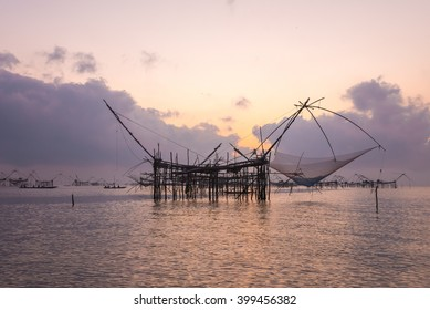 Silhouette the big fish net trap at dawn under romance sky.