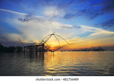 Silhouette the big fish net trap at dawn under sunrise sky at Pak Pra canal, Phatthalung, Thailand.