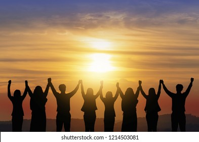 Silhouette of big group of happy friends standing back view  on sunrise background by raised arms together. Happy teamwork ,friendship or teamwork concept.