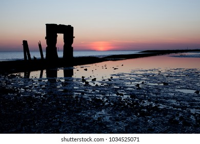 silhouette of a big pillar and wood construction of a demolished bridge on the North Sea coast while deep red sunset