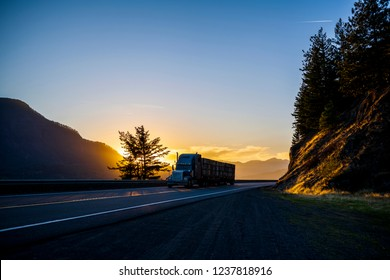 Silhouette of big rig American bonnet powerful classic semi truck transporting stocked fruit boxes on flat bed semi trailer running on highway with mountain in sunset