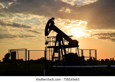 Silhouette of a Big Texan oil pump in action during sunset time