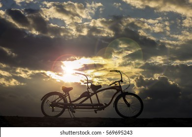 Silhouette of a bike at majestic sunset moment by the beach.