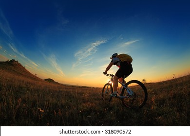 Silhouette of a bike on sky background on sunset