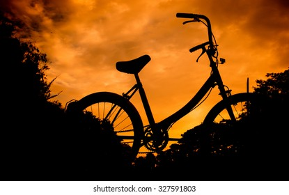 silhouette bike on sunset with orange sky background