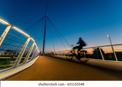 A silhouette of a biker crossing the Hovenring during the end of a beautiful sunset.