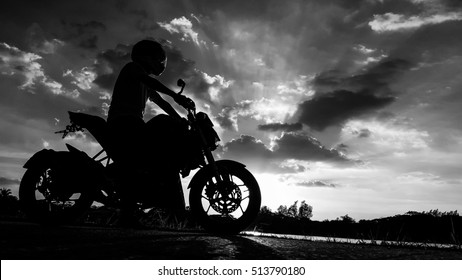 Silhouette biker with his motorbike with beautiful sunset sky. Shoot in black and white shot.