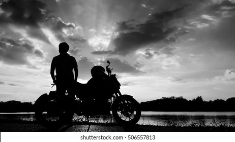 Silhouette biker with his motorbike beside the natural lake and beautiful dramatic sky. Shoot in black and white shot.