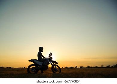 Silhouette biker with his motorbike beside the natural field and beautiful sunset sky.
