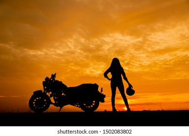 Silhouette of Biker and motorcycle parking with sunset background in Thailand.Young Traveller woman standing and holding helmet beside motorbike.Trip and lifestyle of motorbike concept