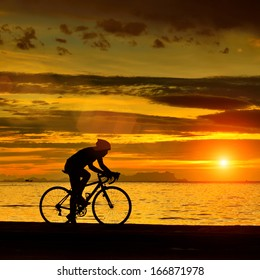 Silhouette of a biker on the beach at dusk.