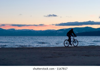 Silhouette of biker riding on beach at sunset