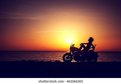 Silhouette of a biker woman resting on the beach on sunset background, enjoying freedom and active lifestyle, having fun on a bikers tour