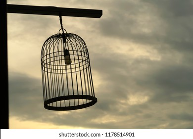 silhouette Bird cage decorated as outdoor light post. Vintage image processed.