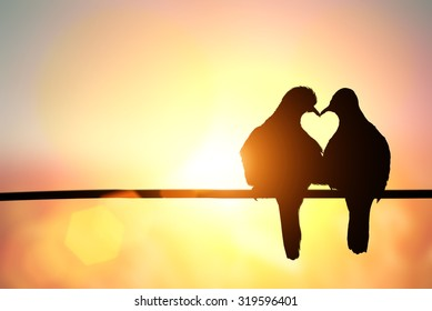 Photo of silhouette of bird in heart shape on pastel background and Valentine's Day