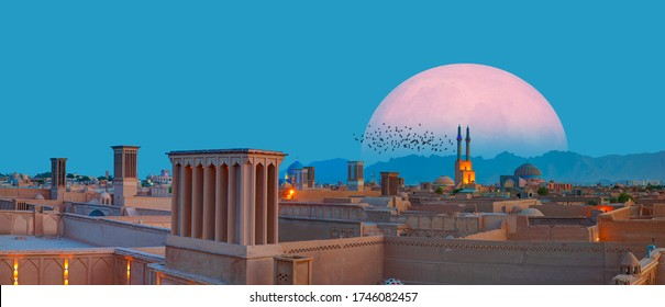 """Silhouette of birds flying - Historic City of Yazd with famous wind towers in the background full moon at twilight blue hour - YAZD, IRAN """"Elements of this image furnished by NASA"""""""