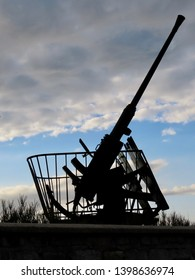 Silhouette of a black anti aircraft gun against blue sky and white clouds. It stands by D-day beach in Arromanches, Normandy, France