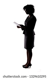 Silhouette of a Black Businesswoman reading a document, report or resume.  She could also be giving a speech and reading a script like a candidate.