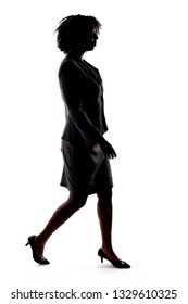 Silhouette of a Black Businesswoman walking in side view isolated on a white background.