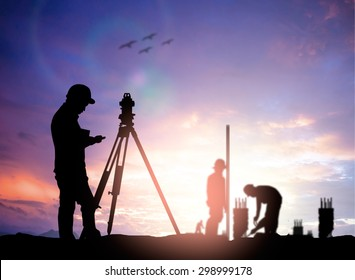 silhouette black man survey civil engineer stand on ground working in a land building site over Blurred construction worker on industrial site.