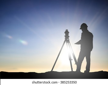silhouette black man survey and civil engineer stand on ground working in a land building site over Blurred construction worker on construction site. examination, inspection, survey