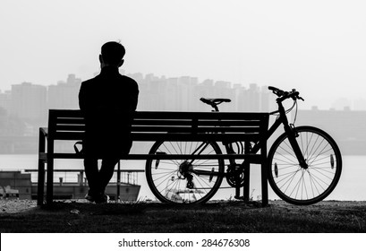 Silhouette in black and white of a man sitting on the bench with his bicycle by the Han river, Korea.