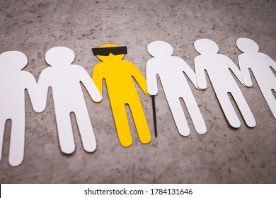 The silhouette of a blind man with a cane and glasses. People stand in a line and support the yellow figure by the hands. A disabled person is a full-fledged part of society.