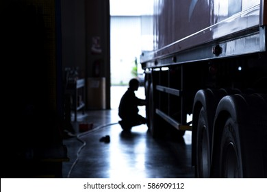 silhouette blur automobile mechanic checking truck in the garage, selective focus and cool tone photograph.
