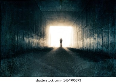 A silhouette of a blurred figure emerging from the light at the end of a dark sinister tunnel. With a grunge, vintage, grainy edit.