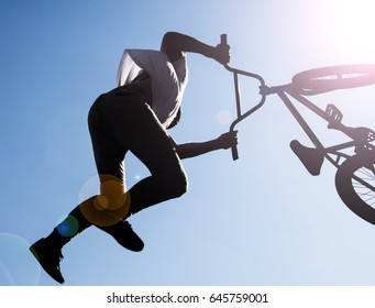 silhouette of bmx rider performing stunts in the air