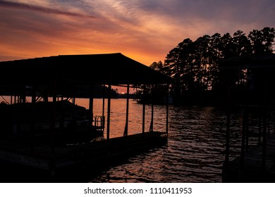 A silhouette of a boat dock at sunset.