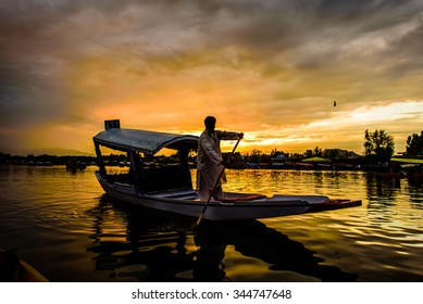 The silhouette of a boat glides along the surface of Dal Lake during sunset with Srinagar Fort in the background in Kashmir, India