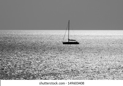The silhouette of a boat in the sea in black and white