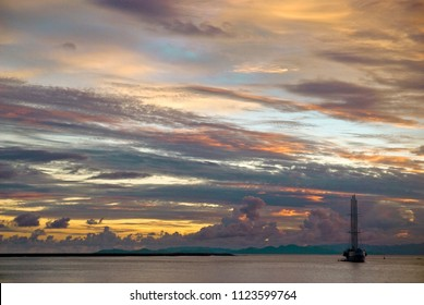 Silhouette of boat in the sea during a sunset with cloud sky and warm colors in Puntarenas beach, Pacific of Costa Rica