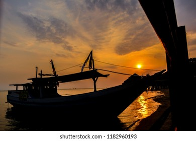 Silhouette of the boat at sunset on the beach of Kartini Jepara, Central Java, Indonesia