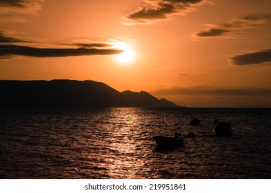 silhouette of boats on sea at sunset