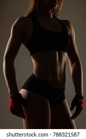 Silhouette bodybuilding girl in sports gloves for fitness posing on background
