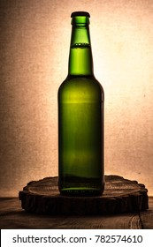 Silhouette of a bottle of beer on a wooden table and fabric back