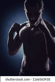 Silhouette of a boxer with clenched fists against a dark background. The concept of boxing