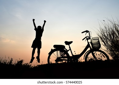 Silhouette boy and bicycle Background sunset