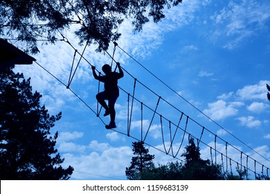 silhouette of boy climbing and taking on the challenge of a high ropes obstacle challenge course