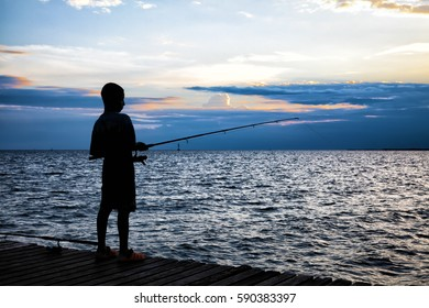 Silhouette of the boy fishing on wooden bridge extended into the sea on sunset.