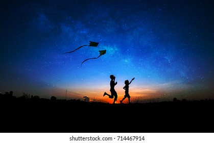Silhouette of boy and girl flying a kite in milky way background.