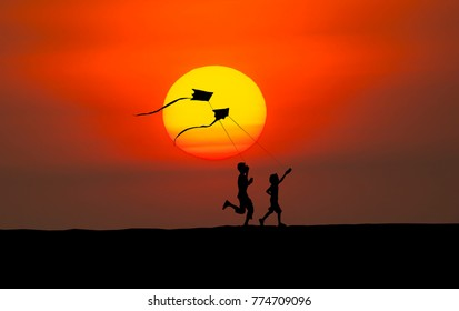 Silhouette of boy and girl flying a kite in sunset background.