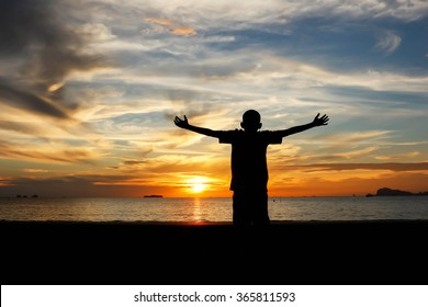 Silhouette of a boy with hands raised on a beach at  the sunset concept for religion, worship, prayer and praise.