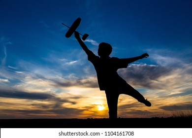 Silhouette of boy with his airplane against sunset, outdoors