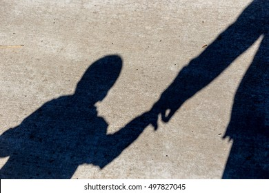 Silhouette of a boy holding a hand