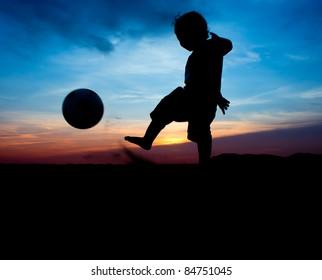 silhouette of boy kick the ball