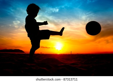 silhouette of boy kick the ball at sunset
